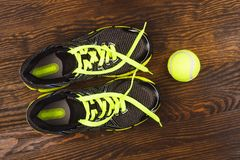 Sneakers and green tennis ball on the wooden background Stock Photos