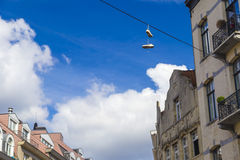 Sneakers hanging from electrical wire against a blue sky in Brussels, Belgium Royalty Free Stock Photos
