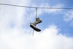 Sneakers hanging on wires on a background of blue sky. royalty free stock image