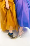 Sneakers and High Heels in Prom Dresses. Just the lower portion of two young girls wearing prom beautiful prom gowns lifting there dresses to reveal one is Royalty Free Stock Photos