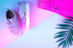Sneakers i sprig drzewka palmowe na modnym neonowym koloru tle, odg?rny widok, lato buty zdjęcie stock