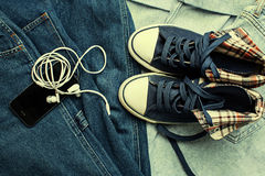 Sneakers, jeans and gadgets. Over jeans Royalty Free Stock Images