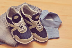 Sneakers, jeans with shirt, on wooden background Stock Photography