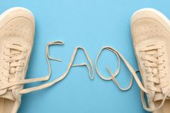 Sneakers with laces in faq text. frequently asked questions concept. New women sneakers with laces in faq text. frequently asked questions concept. Flat lay on stock images