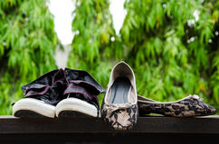 Sneakers and lady shoes put on the wall. Stock Photography