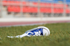 Sneakers lying on a football field. Concept of losing, tired, defeated, fall, pain Stock Image