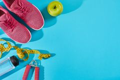 Sneakers with measuring tape on cyan blue background. Centimeter in yellow color near pink trainers, close up. Sport shoes and sportive equipment for healthy Royalty Free Stock Images