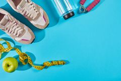Sneakers with measuring tape on cyan blue background. Centimeter in yellow color near white trainers, close up. Sport shoes and sportive equipment for healthy stock image