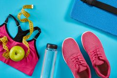 Sneakers with measuring tape on cyan blue background. Centimeter in yellow color, pink sneakers, female sport top and Royalty Free Stock Images