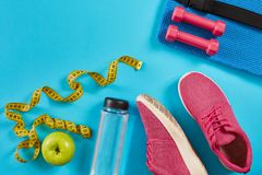 Sneakers with measuring tape on cyan blue background. Centimeter in yellow color, pink sneakers, dumbbells and bottle of Stock Photography