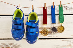 Sneakers and medals on clothesline. Royalty Free Stock Photos