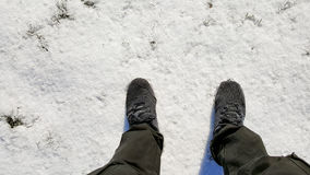 Sneakers men`s stomp on snow. Closeup of sneakers men`s stomp on the ground covered with snow in the winter Stock Photography