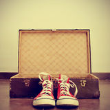Sneakers and old suitcase. A pair of red sneakers in front of an open old brown suitcase with a retro effect Royalty Free Stock Photos