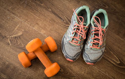 Sneakers and pair of orange dumbbells on wooden background. Weights for a fitness training. Stock Images