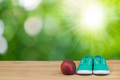 Sneakers and peach on foliage bokeh background Stock Images
