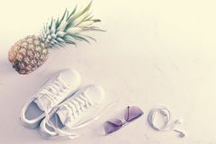 Sneakers, pineapple, sunglasses and headphones royalty free stock image