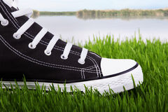 Sneakers on the river bank in green grass Stock Image