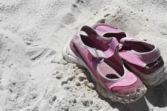 Sneakers in sand. Pink mary jane sneakers sitting in the sand on a beach Stock Images