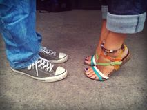 Sneakers and sandals in love. Gray sneakers and colored sandals in love Stock Photos