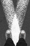 Sneakers stand on asphalt pavement. Royalty Free Stock Photos