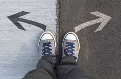 Sneakers standing on a road with arrows. Royalty Free Stock Image