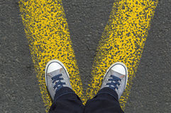 Sneakers standing on the yellow line Royalty Free Stock Photos