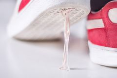 Sneakers stepping in chewing gum on white surface stock photo