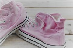 Sneakers for summer. Pink sneakers for summer on a wooden surface Stock Photos