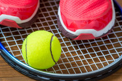 Sneakers and tennis ball on a racket Royalty Free Stock Images