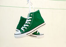 Sneakers tied. Vintage hanging green sneakers tied on pure white background Royalty Free Stock Photo