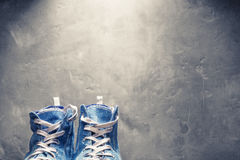Sneakers tip of blue color on a background of concrete wall Stock Photos