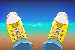 Sneakers on the tropical beach. A pair of shoes on the sandy beach Stock Image
