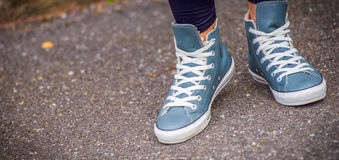 Sneakers walking in really life. Winter blue-gray sneakers in stand by before starting walking in life Stock Image