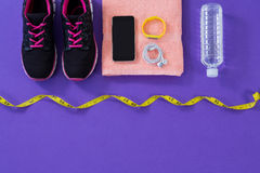 Sneakers, water bottle, towel, measuring tape mobile phone with headphones and fitness band Royalty Free Stock Photos
