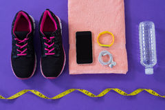 Sneakers, water bottle, towel, measuring tape mobile phone with headphones and fitness band Stock Photography