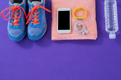 Sneakers, water bottle, towel, mobile phone with headphones and wristband Royalty Free Stock Photos