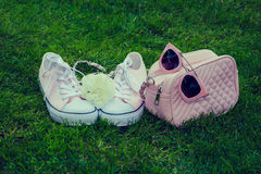 Sneakers with white rose, purse and sunglasses Royalty Free Stock Image