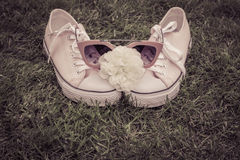 Sneakers with white rose and sunglasses with grass as a backgrou Royalty Free Stock Photo