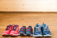 Sneakers for the whole family for sports. On the wooden floor stock images
