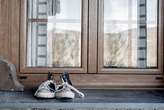 Sneakers on window sill. Frontal perspective. Royalty Free Stock Images