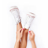 Sneakers on women legs. On white background Stock Image