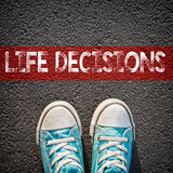 Sneakers and word life decisions. Male sneakers on the asphalt road with drawn word life decisions Stock Photos