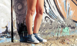 Sneakers worn by the girl standing near the wall with graffiti. Sneakers,  worn by the girl standing near the wall with graffiti Royalty Free Stock Photography