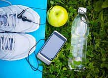 Sneakers on yoga mat  and smartphone with headphones and apple Royalty Free Stock Photography