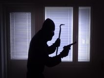 Sneaking burglar with gun and crowbar. Passing window