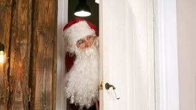 Sneaking Santa Claus secretly entering the living room. Professional shot on Lumix GH4 in 4K resolution. You can use it e.g. in your commercial video, business Stock Photography