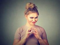 Sneaky, лукавое, замышляя черчение молодой женщины что-то Отрицательные человеческие эмоции, выражения лица Стоковая Фотография RF