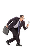 Sneaky businessman looking through a magnifying glass. Isolated on white background Stock Photo