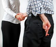 Sneaky Handshake. Image of two people shaking hands with one of them having crossed fingers stock images
