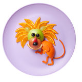 Sneaky lion made of orange and apple. On plate Stock Photos